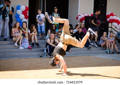 Komsomolsk-on-Amur, Russia, August 1, 2015. a young man dancing a break dance in the square with spectators