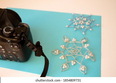 Komsomolsk-on-Amur / Russia - November 9, 2020: Canon camera on the background of a blue leaf and snowflakes made of beads. Photo stocker work during self-isolation.