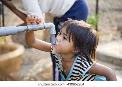 Kon Tum, Vietnam - Mar 29, 2016: A little girl drink water from outdoor tap which water supplied by drilling well in Central Highland of Vietnam. Fresh water is problem in underdevelopment region