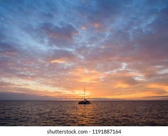 KONA, BIG ISLAND, HAWAII - AUGUST 15, 2018: Sunset over catamaran on west coast of Hawaii