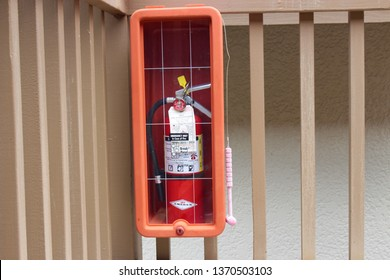 """Kona, Hawaii / USA - April 8th, 2019: A fire extinguisher with the """"emergency only in case of fire"""" message and hammer for breaking the glass at the Kona Coast Resort on the Big Island of Hawaii."""