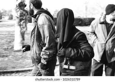 Konak,Izmir,Turkey- January 11, 2017: A radical Islamist couple is walking arm in arm at the street . Woman is wearing burka and man is smoking cigarette at Konak Square in Konak, in Izmir.