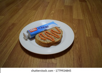 Kongsvinger, Norway - 20 July 2020: Mills Kaviar original sign on tube package isolated traditional Caviar raw fish eggs Norwegian spread on bread slice food on white plate breakfast meal