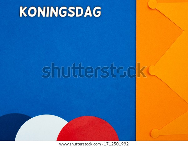 Koningsdag (Kings day) concept with an orange crown and the colors of the Dutch flag, red, white and blue on a blue background. Room for text.