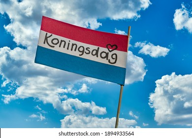 Koningsdag or King's Day is a national holiday in the Kingdom of the Netherlands. Paper cut crown with an inscription koningsdag against the sky