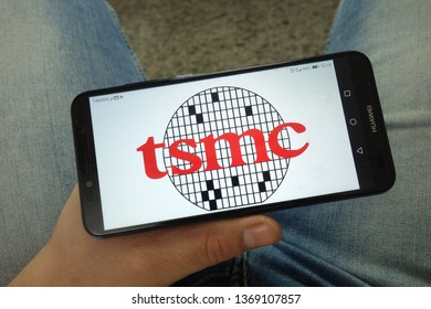 KONSKIE, POLAND - April 13, 2019: Man holding smartphone with Taiwan Semiconductor Manufacturing Company, Limited (TSMC) logo