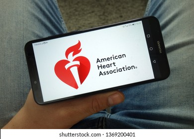 KONSKIE, POLAND - April 13, 2019: Man holding smartphone with American Heart Association (AHA) logo