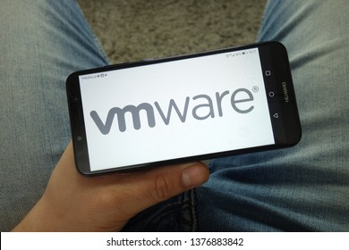 KONSKIE, POLAND - April 13, 2019: Man holding smartphone with VMware, Inc.  company logo