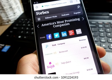 KONSKIE, POLAND - MAY 07, 2018: Man holding his smartphone and scrolling the ranking of America`s most promising companies on the official Forbes magazine website