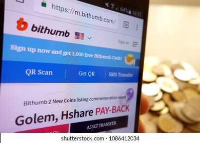 KONSKIE, POLAND - MAY 08, 2018: Bithumb cryptocurrency exchange website displayed on smartphone and stack of coins