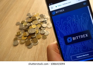 KONSKIE, POLAND - MAY 08, 2018: Bittrex cryptocurrency exchange website displayed on smartphone and stack of coins