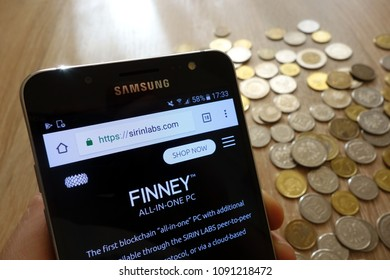 KONSKIE, POLAND - MAY 08, 2018: Sirin labs token cryptocurrency exchange website displayed on smartphone and  stack of coins