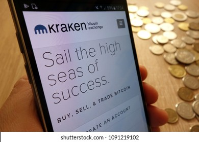 KONSKIE, POLAND - MAY 08, 2018: Kraken cryptocurrency exchange website displayed on smartphone and stack of coins