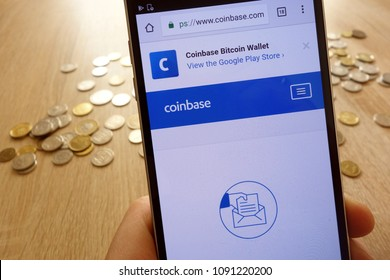 KONSKIE, POLAND - MAY 08, 2018:  Coinbase cryptocurrency exchange website displayed on smartphone  and stack of coins