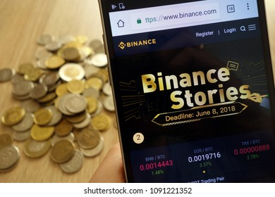 KONSKIE, POLAND - MAY 08, 2018: Binance cryptocurrency exchange website displayed on smartphone and  stack of coins