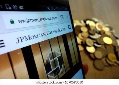 KONSKIE, POLAND - MAY 14, 2018: JP Morgan Chase website displayed on smartphone and stack of coins