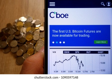 KONSKIE, POLAND - MAY 14, 2018: CBOE Global Markets website displayed on smartphone and stack of coins