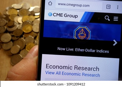 KONSKIE, POLAND - MAY 14, 2018: CME Group website displayed on smartphone and stack of coins