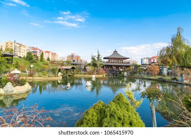 KONYA, TURKEY - NOVEMBER 11, 2017 : Landscape view of Kyoto Japan Garden in Konya with small lake and wooden buildings around, among big apartments on cloudy sky background.