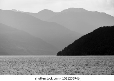 Kootenay Lake, British Columbia, Canada.  Haze over the lake and mountains on a summer morning in monochrome.