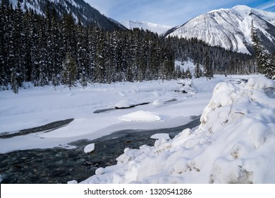 The Kootenay River in Kootenay National Park is covered in snow and ice during winter. Taken near Numa Falls waterfall