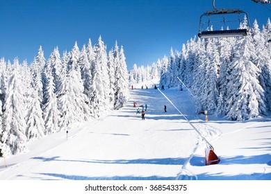 Kopaonik, Serbia - January 19, 2016: Ski resort Kopaonik, Serbia, ski slope, ski lift, skiers on the piste among white snow pine trees forest