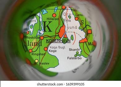 København, Kopenhagen, the capital of Danmark, seen through binoculars focused on an old map of Europe.