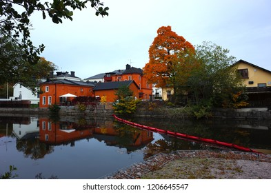 Koping, Sweden - 4 October, 2018: Traditional red residential building and autumn color tree reflecting on calm surface of the river