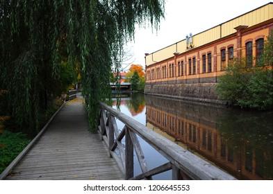 Koping, Sweden - 4 October, 2018: Old industrial building and wooden walkway next to river