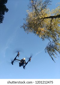 Kopter (drone) flying in the blue sky, propellers rotate, leaves and treetops are visible