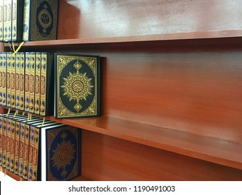 Koran assorted in rows on wooden shelf with copy space for text advertising. Arabic word translation : The Holy Al Quran (holy book of Muslims) - it's public item of all muslims. Islamic concept