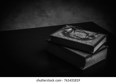 Koran - holy book of Muslims ( public item of all muslims ) on the table , still life . Monochrome or black and white