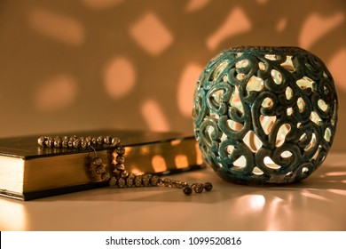 Koran and rosary beads on the white background with blue candle for Islamic concept. Holy book quran for Muslims holiday, Ramadan,blessed Friday message and three months.