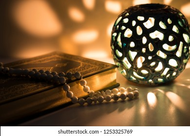 Koran and rosary beads on the white background with blue candle,lantern for Islamic concept. Holy book quran for Muslims holiday, Ramadan,blessed Friday message and three months.