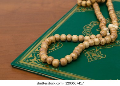 Koran and rosary beads on the wooden background for Islamic concept. Holy book quran for Muslims holiday, Ramadan,blessed Friday message and three months.