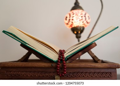 Koran and rosary beads on the wooden background with lantern or candle for Islamic concept. Holy book quran for Muslims holiday, Ramadan,blessed Friday message.