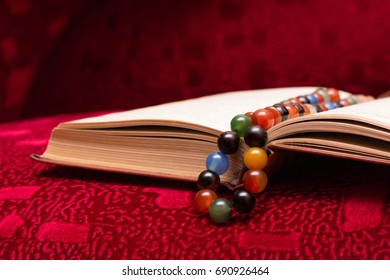 Koran and rosary beads. open book Quran religion of Islam on red background. Concept of enlightenment, acceptance of faith.