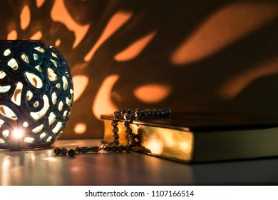 Koran and rosary beads with soft light lantern for Islamic concept. Holy book Quran for Muslims for Ramadan,blessed Friday message and three months.