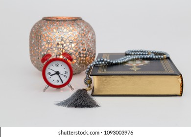 Koran,red clock and rosary on the white background with soft lantern light for Islamic concept and blessed Friday message. Holy book Quran for Muslims for eleven month sultan  Ramadan.