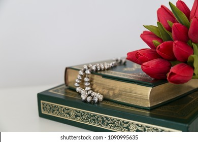 Koran,tulips and rosary beads on the white background for Islamic concept. Holy book Quran for Muslims for Ramadan,happy blessed Friday message and three months.
