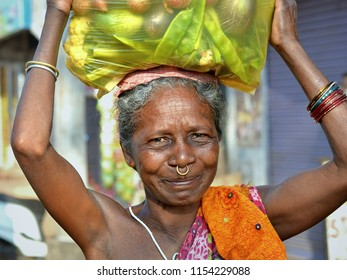 KORAPUT, ODISHA / INDIA - DEC 4, 2016: Smiling elderly Indian Adivasi tribal woman with one golden nose ring carries on her head a heavy plastic bag with assorted fresh vegetables, on Dec 4, 2016.