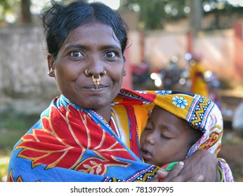 KORAPUT, ODISHA/INDIA - DEC 4, 2016:  Young Indian Adivasi mother (Dongria Kondh tribe) with distinctive tribal nose jewelry holds a sleeping baby in her arms at Koraput tribal market, on Dec 4, 2016.