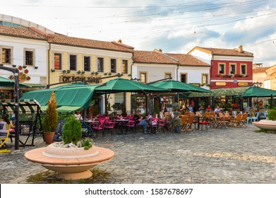 Korce, Albania - July 14, 2019: Old Bazaar of Korca city with people hanging out at cafes during summer evening.