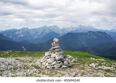 Kordezeva Glava / Peca hill, Karavanke mountain range, Slovenia / Austria - Stone barrow and beautiful scenery from the top of hill. Peaks of mountains of Alps in the background
