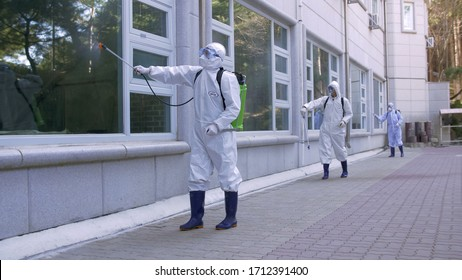Korea, April 13, 2020. Workers in protective suits spray disinfectants on windows and floors outside apartment buildings in residential areas. Health measures to prevent Covid-19 in isolated community
