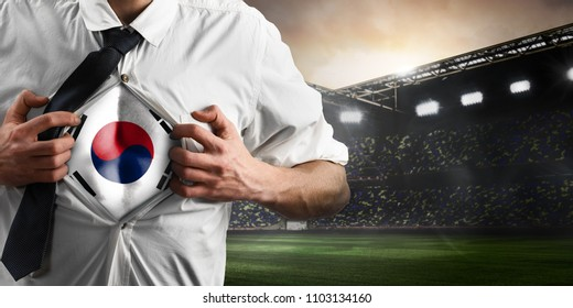 Korea soccer or football supporter showing flag under his business shirt on stadium.