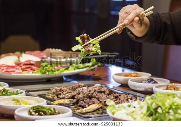 Churrasco coreano Bulgogi carne bovina e alface realizada com pauzinhos