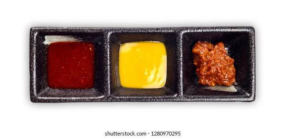 Korean BBQ-Salty and sweet pepper sauce/gochujang sauce and Korean Traditional Sources Ssamjang on black plate. Top view, isolated on white background.