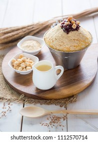 Korean bean Bingsu, sweet milk dessert serve on wood tray and stainless bowl with red bean.