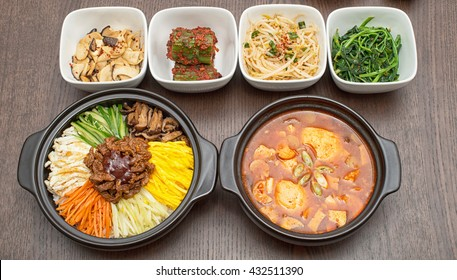 Korean bibimbap and kim-chi soup with side dishes on wooden table